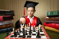portrait of smart girl in graduation cap playing chess - stock photo