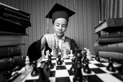 Monochrome portrait of girl graduation hat playing chess Kuvituskuvat