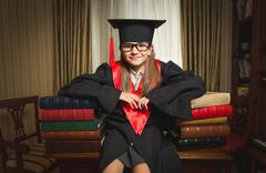 Genius girl in graduation clothes leaning on books at library Stock Photos