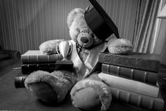 Monochrome shot of teddy bear in graduation hat sitting on table Kuvituskuvat