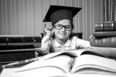 portrait of smart girl in graduation hat sitting at desk full of books - stock photo