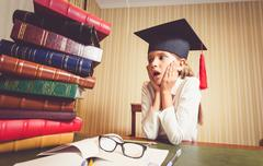 amazed smart girl in graduation cap looking at big heap of books - stock photo
