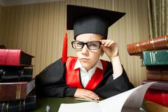funny girl in graduation cap and eyeglasses looking at camera - stock photo