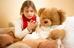 girl playing and measuring teddy's bear temperature with thermometer - stock photo