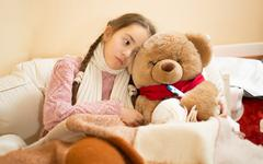 sick girl resting in bed with brown teddy bear - stock photo