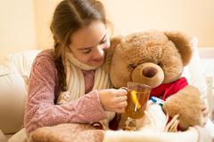 Closeup of little sick girl giving hot tea to teddy bear - stock photo