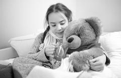 portrait of cute girl lying in bed and giving pills to teddy bear - stock photo