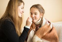 Young mother giving medicines on spoon to daughter caught flu Kuvituskuvat