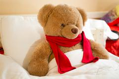 Closeup of brown teddy bear in red scarf lying in bed - stock photo