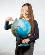 cute smiling girl pointing at Earth globe against white background - stock photo