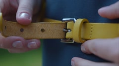 young woman buttoning leather strap at the waist - stock footage