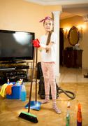 Girl cleaning up living room with vacuum cleaner, swab and scoop Stock Photos