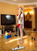 Teenager girl cleaning floor at living room with swab Stock Photos
