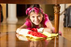 Portrait of smiling girl polishing wooden table with cloth - stock photo