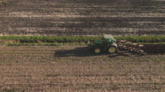 Aerial: Passing a Farmer Cultivating a Field Stock Footage
