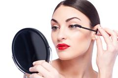 Attractive young woman is doing facial make-up - stock photo