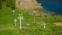 funicular at sports base on the backdrop of green hills and lakes - stock photo