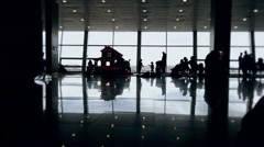 Silhouettes of children playing in playground of modern airport waiting hall - stock footage