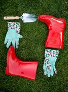garden gloves, spade and red rubber boots lying on green grass - stock photo