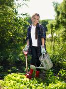 Smiling girl working at garden with shovel and watering can Kuvituskuvat