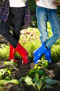 Two girls in gumboots posing on garden bed at hot summer day Stock Photos