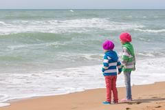 Two girls holding hands standing on the beach and looking into the distance Stock Photos