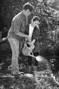 Black and white photo of young father and daughter watering garden bed - stock photo