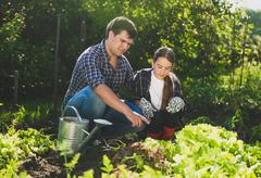 man sitting at garden with daughter and teaching her horticulture - stock photo