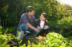 smiling father teaching daughter horticulture at garden - stock photo