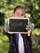 "Girl holding blackboard with text ""Garden"" under the tree Stock Photos"