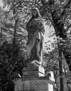 Old statue on grave - stock photo