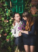 man sitting on porch with pregnant wife and giving her flowers - stock photo