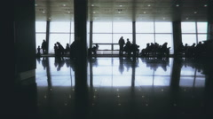 Silhouettes of passengers walking with luggage in airport waiting room - stock footage