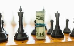 Closeup of rolled dollars on place o black chess piece Stock Photos