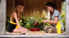Balinese woman showing european woman-tourist how to make offerings Stock Footage