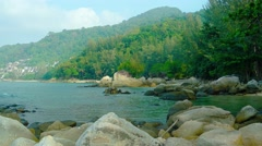 Tranquil Tropical Bay with Boulders and Forested Mountainside Stock Footage