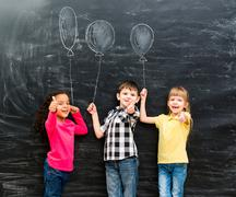 three smiling children with thumbs up keeping imaginaru drawn balloons - stock photo