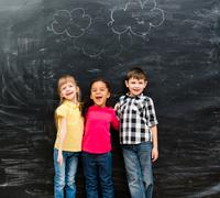 three different laughing children with blackboard on background - stock photo