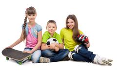Three cute children sitting on the floor with sport equipment Stock Photos