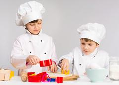 Two smiling children in the kitchen Stock Photos