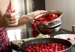 Housewife making cherry jam in metal saucepan Stock Photos
