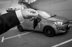 black and white photo of man in suit holding car keys against new car - stock photo
