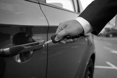 Black and white closeup of man inserting car key in the hole Stock Photos
