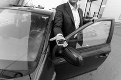 Black and white closeup of car sales manager holding key on hand - stock photo
