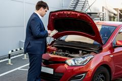 manager checking car condition on tablet - stock photo