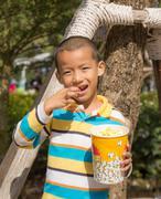 Asian boy eating eating popcorn Stock Photos