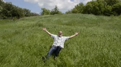 Mature bald man is funny demonstrating how to fall into the grass. - stock footage