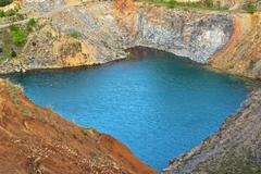 the emerald lake in old abandoned basalt quarry, Racos, Romania - stock photo