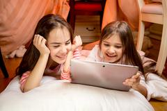 Two happy smiling girls lying on floor and using digital tablet Stock Photos