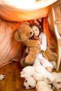 Little girl playing with teddy bear in self-made house Stock Photos